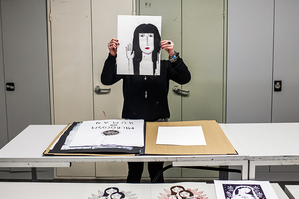Joanna Winograd holding a self portrait in front of her face