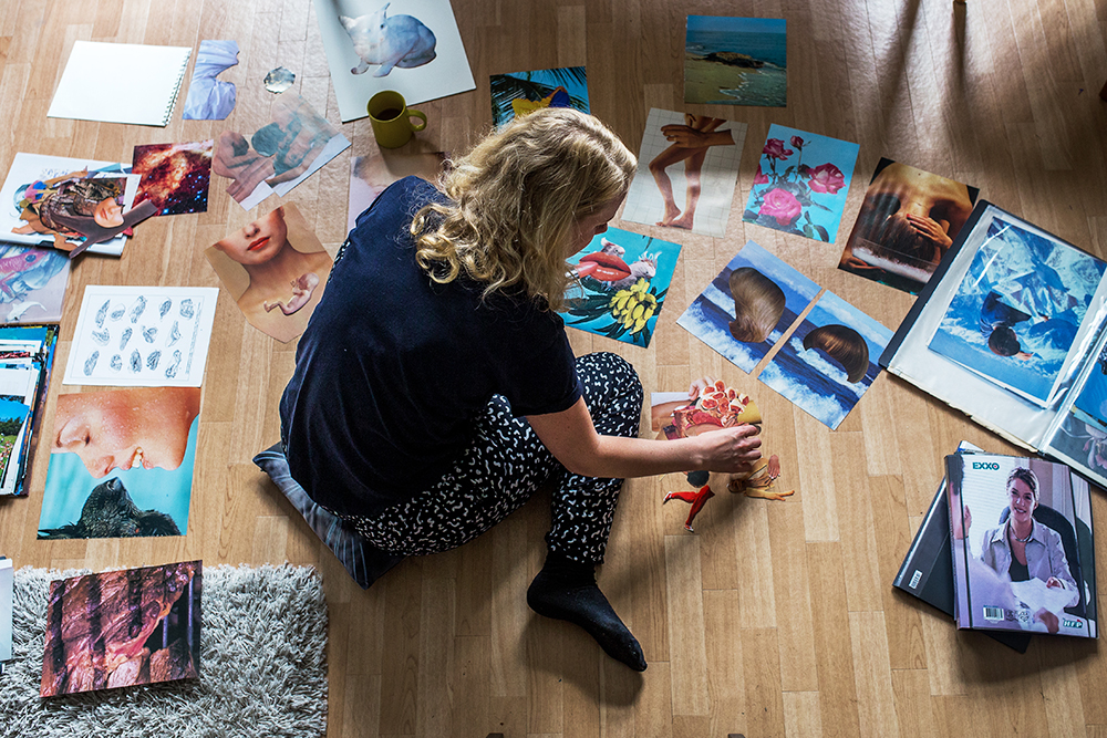 Megan Archer sitting on the floor working on collages