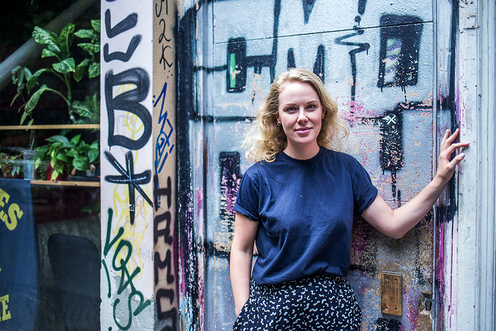 Megan Archer standing in front of a grafitti wall