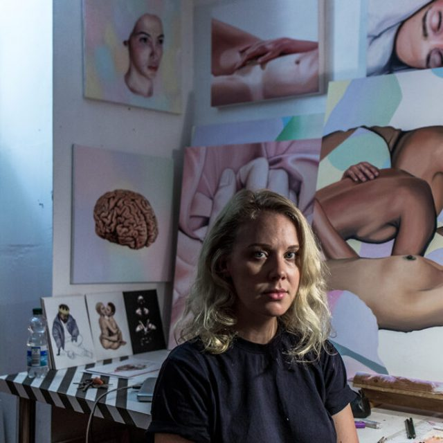 Megan Archer sitting in front of her paintings
